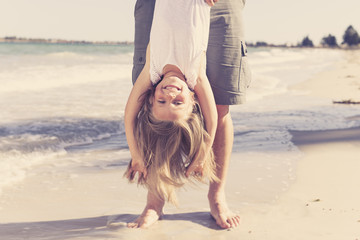 father holding sweet young and lovely blond small daughter by her feet playing having fun on the beach in dad and little girl love concept