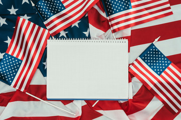 top view of arranged american flags and blank notebook, presidents day concept