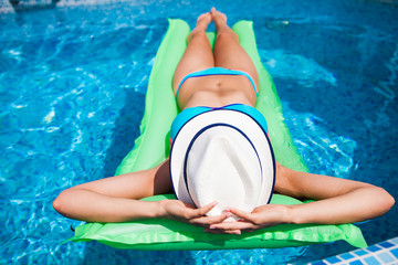 Woman relaxing on mattress in the pool water in hot sunny day. Summer holiday idyllic.