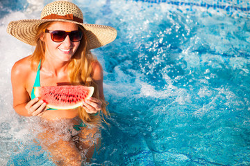 A girl holds half a red watermelon  over a blue pool, relaxing on spa in a tropical hotel, eating healthy, fruit diet, summer style