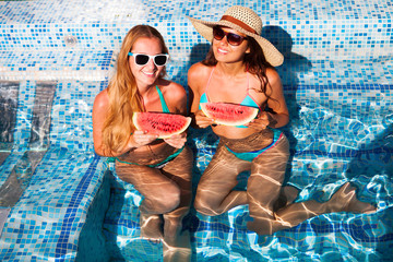 Girlfriends holds half a red watermelon  over a blue pool, relaxing on spa in a tropical hotel, eating healthy, fruit diet, summer style