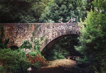 Mother and son sit on old viaduct bridge over the forest river