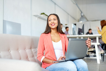 happy woman with laptop working at office