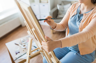 artist with brush painting at art studio