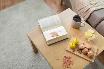 Fototapete - book, lemon, tea and cookies on table at home