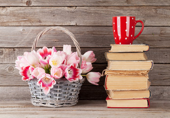 Pink tulips bouquet, books and coffee cup