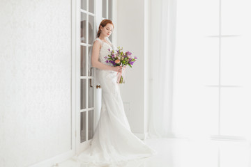 Tender bride standing in a bright room by the door, she waits for the groom.
