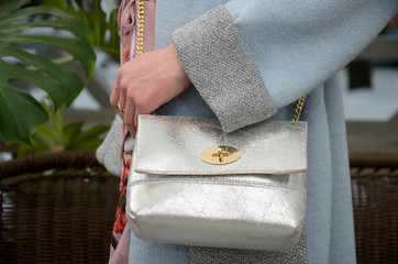 elegant small silver leather bag in the hands of a fashionista.