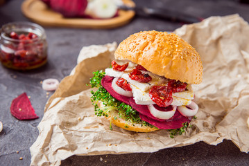 Vegitarian burger with beet slices, microgreen sprouts, tofu cheese, dried tomatoes and onion on kraft package paper on dark stone background with inhrediants. Soft selective focus. Copy space.
