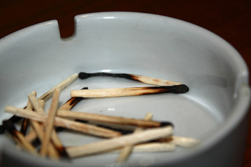 Burned matches in a porcelain ashtray
