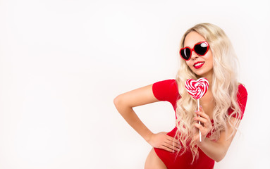 Beautiful young woman in red swimsuit holds lollipop. Copy space. Sexy girl with candy. Sunglasses of the heart.