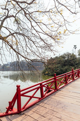 Red Bridge at Hoan Kiem Lake with tress and reflected shadow and branches in foreground in Hanoi, Vietnam.