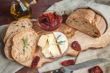 Bread whole wheat processed cheese Camembert with sun-dried tomatoes with rosemary and olive oil.