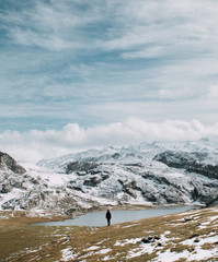 Hiker standing at lake in hills