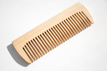 Thin comb of light wood on a white background