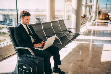 Young business man sitting on the computer with the suitcase at the airport waiting for the flight