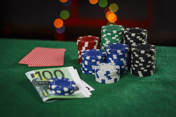 Poker chips, euros and cards on the green table
