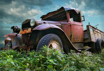An old vintage rustic red colored truck on a field with cloudy sky background