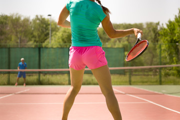 Girl playing with a racket in tennis on the court
