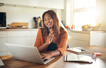 Smiling woman working online at her kitchen table at home