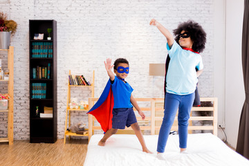 African American happy and confident young kids playing and dressing up as superhero together in bedroom.