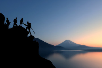 Male and female hikers climbing up silhouette mountain cliff and one of them giving helping hand. People helping and, team work concept