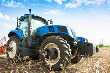 Two blue tractors in the empty field.