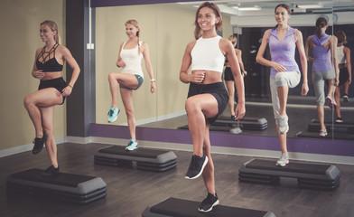 Women doing step aerobics exercises