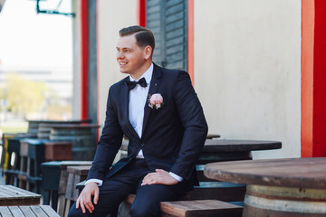 Portrait of a stylish groom in the city
