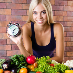 Happy woman in fitness wear with vegetarian food