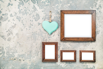 Wooden photo or picture frames blanks and handmade Valentine's day love heart hanging on vintage aged grunge textured concrete wall background. Retro old style filtered photo