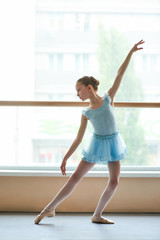 Young ballerina in blue dress practicing in studio. Cute ballet girl training ballet dance in class. Lovely ballet artist.