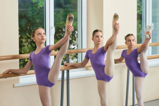 Cute young ballerinas stretching legs. Legs lift of young beautiful ballerinas at ballet barre, window nature background.