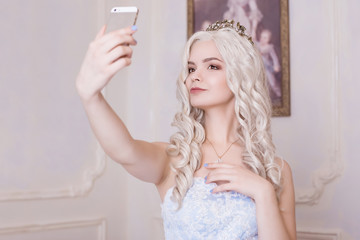 A glamorous girl, a blond woman in a crown, makes a selfie. Spoiled girl, a daughter of an oligarch. Photograph on an expensive smartphone, narcissist. Princess on the background of the picture.