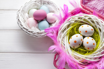 White and colored Easter eggs in basket on white wooden background