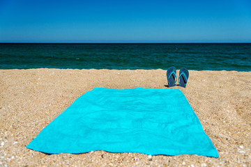 Blue sandal flip flop and towel on yellow sand. Summer fun time and accessories on the beach, summer vacations