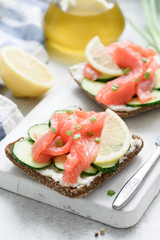 Salmon toast with cream cheese and cucumber on white cutting board. Healthy snack, appetizer. Selective focus