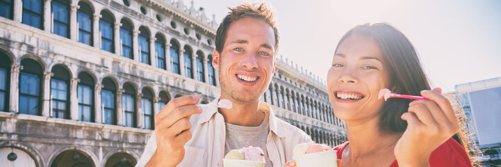 Happy couple tourists eating gelato ice cream on San Marco Square in Venice, Italy, Multiracial Asian woman Caucasian man on summer travel vacation, italian food lifestyle. Panoramic banner.