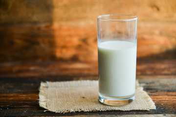 glass of milk with napkin on old wooden table