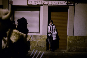 A woman watches from a doorway as people dressed as Momotxorros, half bull, half man figures dressed in blood soaked sheepskins, take part in carnival celebrations in Alsasua
