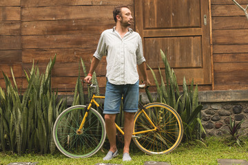 Modern guy standing with old bicycle in tropical garden.