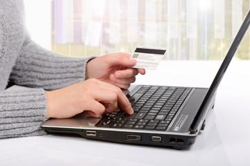 Karta kredytowa w dłoni, zakupy w sklepie internetowym przy pomocy komputera. - fototapety na wymiar