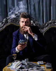 Businessman with beard has cigar, champagne and dollars.