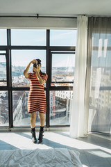 Full length of young woman photographing with camera while standing against windows at home