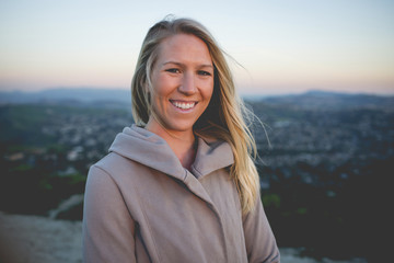 Portrait of smiling woman standing on mountain against sky during sunset