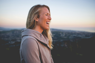 Side view of happy woman standing on mountain against sky during sunset