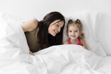 Smiling mother and daughter sitting on bed at home