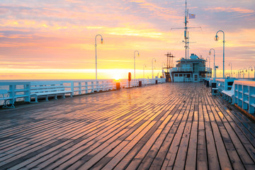 The first rays of the sun warms the wet boards of the pier in Sopot. Poland.