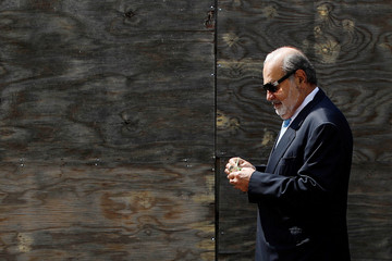 Mexican billionaire Carlos Slim holds money as he walks on a street after attending a ceremony to place the first stone of the new U.S. Embassy, in Mexico City