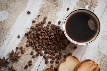 coffee cup, coffee beans of toast scattered on the rough wooden surface background